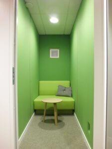 Ljuddämpande väggbeklädnad med grönt ylletyg i telefonbås.