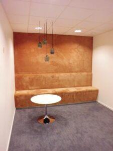Klädsel av väggfast soffa med heltäckningsmatta, där mattan går ända upp till tak.