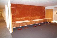 Klädsel av väggfast soffa med tuftad heltäckningsmatta, där mattan går ända upp till tak.