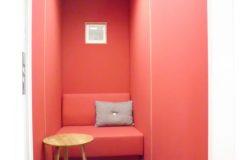 Ljuddämpande väggbeklädnad med rosa ylletyg i telefonbås.